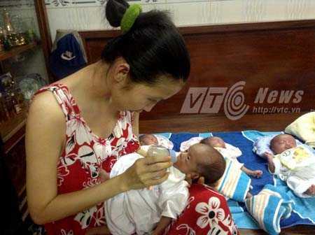 Chị Thư cho các con bú sữa bình, xoay bận liên tục hết bé này đến bé khác. Ảnh: Phan Cường
