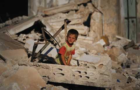 Một cậu bé Syria bên cạnh đống đổ nát sau những cuộc giao tranhgiữa quân chính phủ và phe nổi dậy