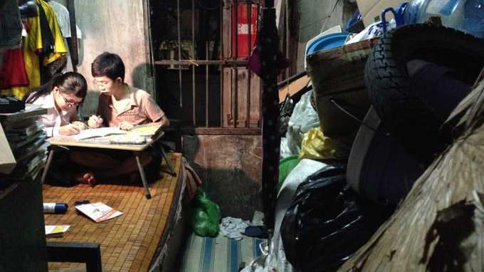Việt Thắng chỉ em học. Căn gác nhỏ xíu bề bộn vỏ xe cũ, chai lọ, quần áo cũ... - của để dành của gia đình