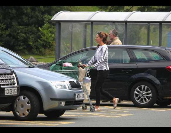 Kate sải bước nhanh nhẹn trên phố thanh bình ở thị trấn Anglesey, Wales.
