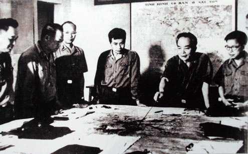 Quân ủy Trung ương đang theo dõi diễn biến Chiến dịch Hồ Chí Minh năm 1975. Trong ảnh, từ trái sang phải: đại tá Lê Hữu Đức (Cục trưởng Cục tác chiến), thượng tướng Hoàng Văn Thái (Phó tổng tham mưu), thiếu tướng Vũ Xuân Chiêm (Phó chủ nhiệm Tổng cục Hậu cần), thượng tướng Song Hào (Chủ nhiệm Tổng cục Chính trị), đại tướng Võ Nguyên Giáp (Tổng tư lệnh, Bộ trưởng Quốc phòng, Bí thư Quận ủy Trung ương), trung tướng Lê Quang Đạo (Phó Chủ nhiệm Tổng cục Chính trị).