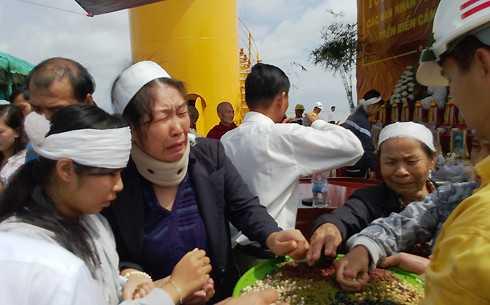 Thân nhân rắc gạo, muối, đậu xuống bến Gò Công Đông. Ảnh: VNE