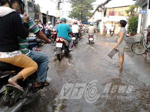 Xắn quần lội nước cùng xe máy. Ảnh: Phan Cường