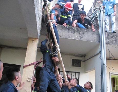 Lực lượng chức năng đưa cô gái từ tầng thượng xuống