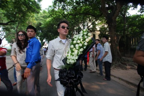Nam ca sĩ Đàm Vĩnh Hưng cầm trên tay bó hoa trong dòng người vào viếng Đại tướng Võ Nguyên Giáp.