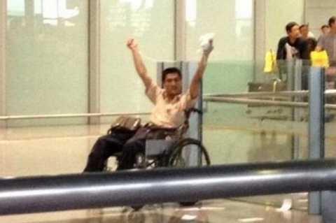 Ký Trung Tinh đi xe lăn và cầm gói thuốc nổ trên tay