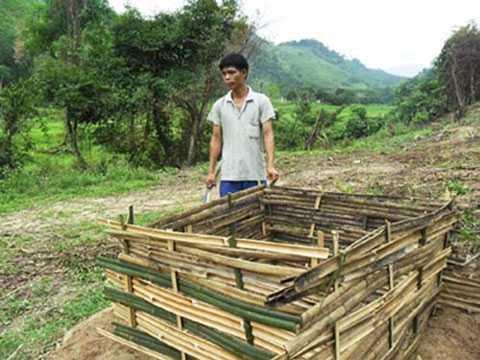 Người chồng trẻ Triệu Đức Long đang giúp vợ làm chuồng gà ở phía rìa rừng sau nhà.