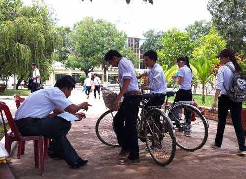 Thầy quản sinh kiểm tra đồng phục học sinh trước khi vào lớp học
