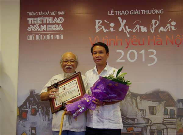 Ông Nguyễn Đức Lợi - Tổng Giám đốc TTXVN trao Giải thưởng Lớn Vì tình yêu Hà Nội cho nhà nhiếp ảnh Quang Phùng.