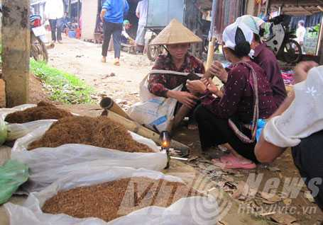 Một số phụ nữ đứng tuổi ở Lạc Sơn vẫn thường hút thuốc làogiữa chợ