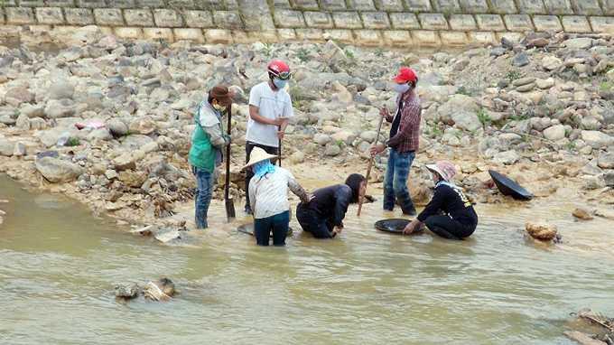 Một nhóm học sinh cấp III đãi vàng trên sông A Vương đoạn chảy qua thị trấn Tơ Viêng - Ảnh: THANH BA