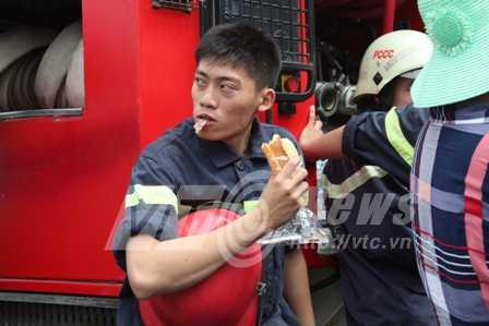 Một chiến sĩ PCCC dùng nhanh ổ bánh mì để tiếp tục công việc tìm kiếm nạn nhân (Ảnh: Phạm Nguyễn)