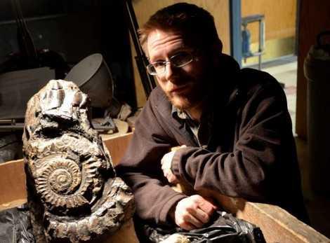 Nhà địa chất học Leif Tapanila bên cạnh hóa thạch hàm răng của Helicoprion