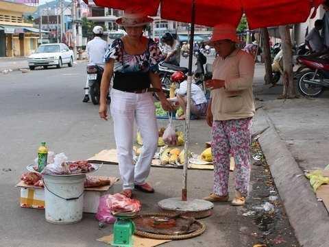 Heo rừng và các mặt hàng tràn xuống lòng đường trước chợ Vĩnh Hải. Người phụ nữ này cả tin mua về cho chồng ăn với hi vọng sẽ... hên cả năm. Ảnh: Lưu Thái Văn Chương