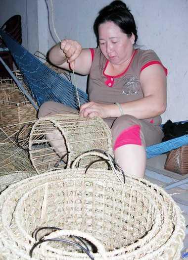 Gần nửa đêm, bà Bích vẫn cặm cụi đan hàng để kịp giao trước Tết. Ảnh: Ái Nam