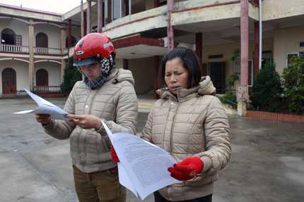 Bà Thương, bà Hiền đang xem bản kết luận của Cơ quan CSĐT giao tại trụ sở UBND xã Vinh Quang - Ảnh Minh Khang