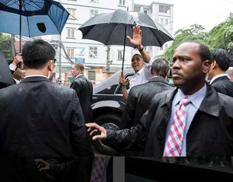 Tổng thống thứ 44 của Mỹ cầm ô và vẫy chào người dân Hà Nội trước khi lên xe ra sân bay Nội Bài để di chuyển vào TP HCM.