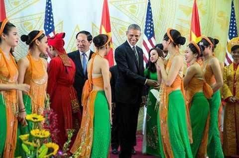 Ông Obama tươi cười, trò chuyện với thành viên đoàn ca múa nhạc khi dự tiệc do Chủ tịch nước Trần Đại Quang chủ trì tại Trung tâm Hội nghị Quốc gia ngày 23/5.