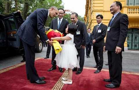Người đứng đầu Nhà Trắng rạng rỡ nhận bó hoa từ bé Vũ Phạm Phương Linh - đại diện cho thiếu nhi Việt Nam trong lễ đón tại Phủ Chủ tịch.