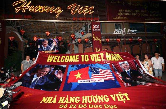 Nhiều người mang sẵn băng-rôn chào mừng vị tổng thống Mỹ - Ảnh: Quang Minh