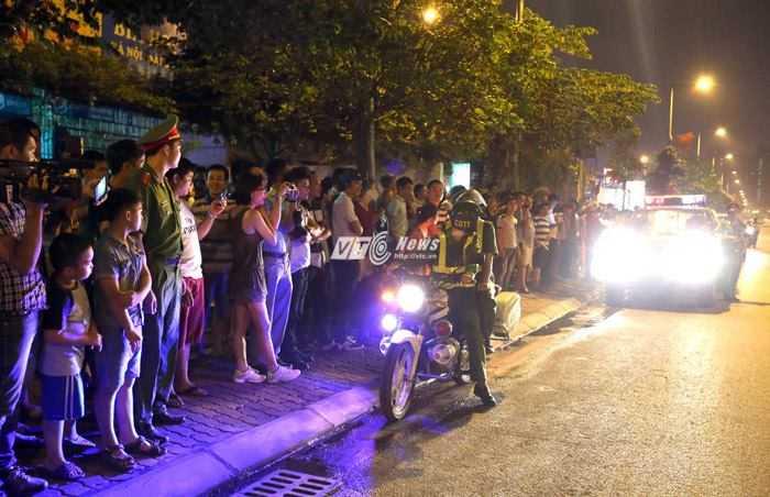 Lực lượng chức năng nhắc nhở người dân giữ trật tự trong khi chờ đợi - Ảnh: Quang Minh