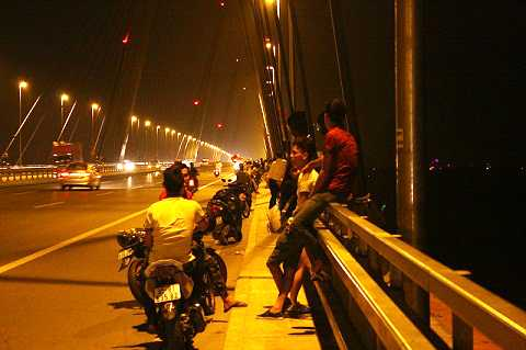 Bất chấp nguy hiểm rình rập, bụi khói ô tô mù mịt, nhiều người vẫn ngồi vắt vẻo trên cầu Nhật Tân để hóng gió, thậm chí còn đu ra khỏi hành lang an toàn để tâm sự.