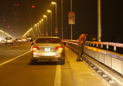 Những chiếc ôtô được bật đèn tín hiệu khẩn cấp, nằm chình ình chiếm hết phần đường dành cho xe máy. Chủ nhân của chúng thì vô tư đứng hóng gió trên cầu mặc cho phương tiện của họ đang cản trở giao thông.
