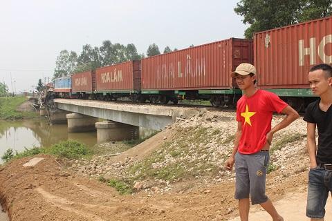 Xe tải bị tàu hỏa kéo lê một khoảng 50m, tông bay hàng rào sắt lan bảo vệ hai bên đường ray