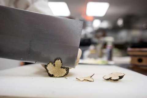 Một trong những nguyên liệu chính làm   nên bát mỳ đắt giá là thịt bò Kobe trứ danh được nhập trực tiếp từ Nhật   Bản, nấm cục và những miếng vàng mỏng 24-karat. Ảnh: Đầu bếp thái nấm   cục, loại nấm đắt nhất thế giới, để chuẩn bị cho món ăn kèm mỳ.