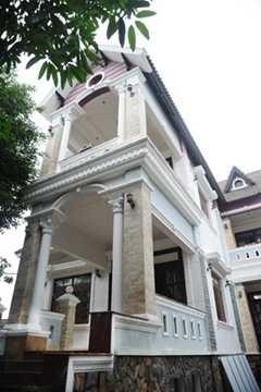Cơ ngơi của Minh Béo bề thế với hai tầng lầu và xung quanh là cây cối xanh tươi.