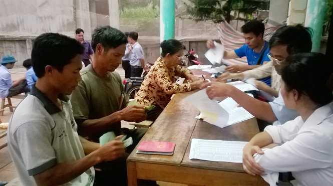 Các hộ nuôi cá lồng bị thiệt hại nặng đang nhận tiền đền bù từ Công ty cổ phần Mía đường Hòa Bình- Ảnh: Hà Đồng