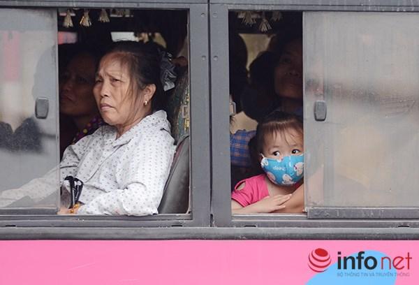 Một em nhỏ mệt mỏi khi phải ngồi trong một xe khách chở quá người nên phải mở cửa kính ra cho thoáng.