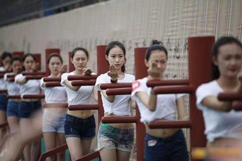 Các nữ học viên trong trang phục áo phông, quần sooc tập luyện với cột.
