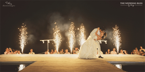 Lễ cưới chính được tổ chức ngoài   trời, tiếp theo đó là dạ tiệc bên bể bơi trong khuôn viên resort. Hoa   hồng, cát tường và hoa baby trắng đính trên ghế của khách mời. Tiệc tối   được tổ chức bên bể bơi sát biển. Những dãy bàn tiệc dài trang trí theo   phong cách rustic nhẹ nhàng, trẻ trung.