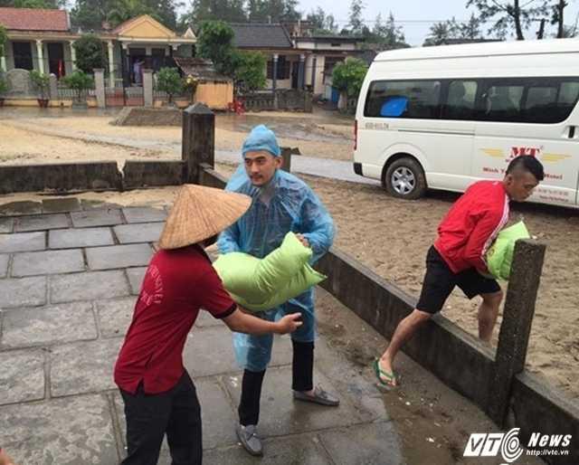 Vận chuyển gạo từ xe vào nhà để trao cho ngư dân.