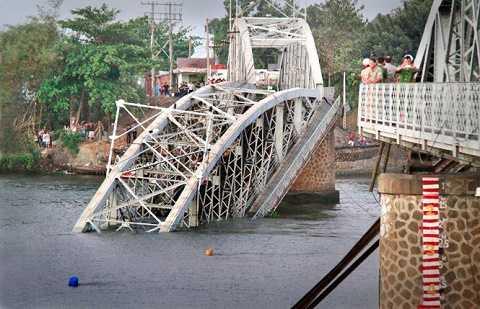 Cầu Ghềnh 112 tuổi bắc qua sông Đồng Nai bị sà lan đâm sập trưa 20-3 làm gián đoạn tuyến đường sắt Sài Gòn - Biên Hòa - Ảnh: Xuân An