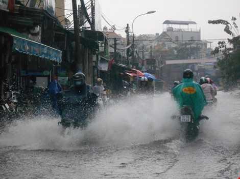 ước ở đường Lê Văn Việt ngập đến nửa bánh xe sau trận mưa chiều nay, dòng nước đen ngòm, gây mùi hôi thối. ẢNH: THANH TUYỀN