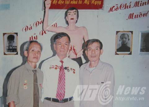 Ông Nghị (ngoài cùng bên phải) trước bức tượng tái hiện hành động đấu tranh năm xưa của mình