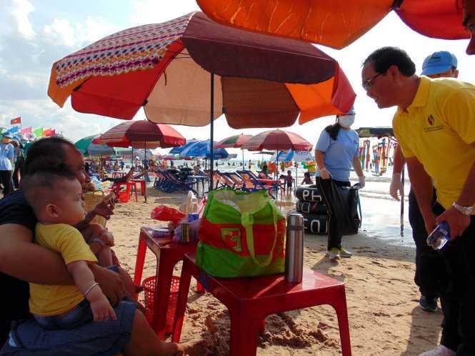 Ông Mai Ngọc Thuận - Bí thư Thành ủy Vũng Tàu (áo vàng) - xuống các bãi tắm, đến tận từng bàn du khách vận động không ăn nhậu, xả rác - Nguồn ảnh: Tuổi trẻ