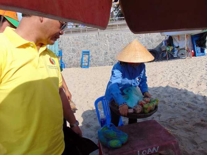 Ông Mai Ngọc Thuận vận động một người bán hàng rong tại bãi sáng 30/4 - Nguồn ảnh: Tuổi trẻ
