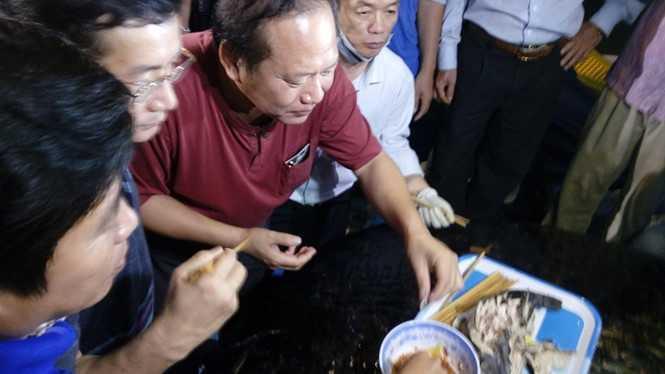 Bộ trưởng Trương Minh Tuấn cùng mọi người dùng cá tươi ngay trên cảng Nhật Lệ- Nguồn ảnh: Thanh Niên