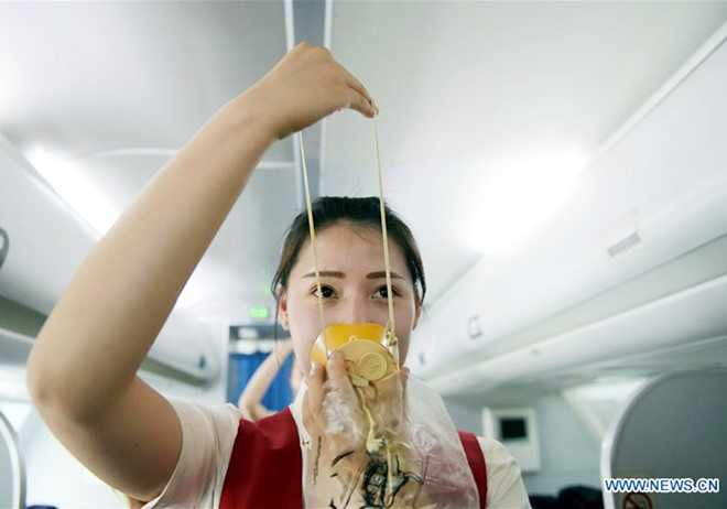 Một nữ sinh năm hai biểu diễn các thao tác an toàn trên máy bay. Là tiếp   viên hàng không, họ cũng phải học cách phản ứng nhanh trong tình huống   khẩn cấp.
