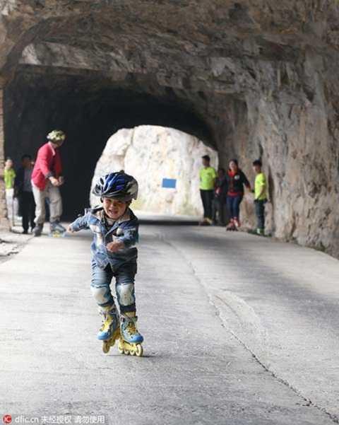 Cậu bé 4 tuổi tự tin di chuyển  bằng đôi giày trượt patin trên đoạn đường ở vách núi. Ảnh Chinadaily