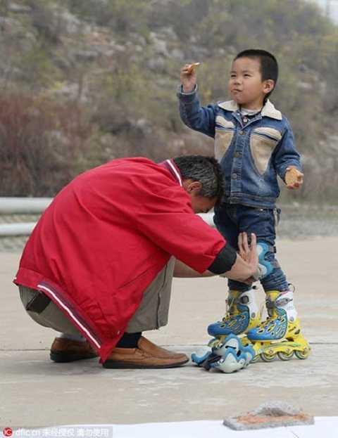Bố của Zhang Jiabo đang giúp cậu bé kiểm tra đôi giày trượt