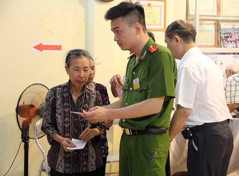Bà Nguyễn Thị Nhâm được các cán bộ ở tổ bầu cử hướng dẫn, giúp đỡ trong quá trình bỏ phiếu (Ảnh: Phạm Thịnh)