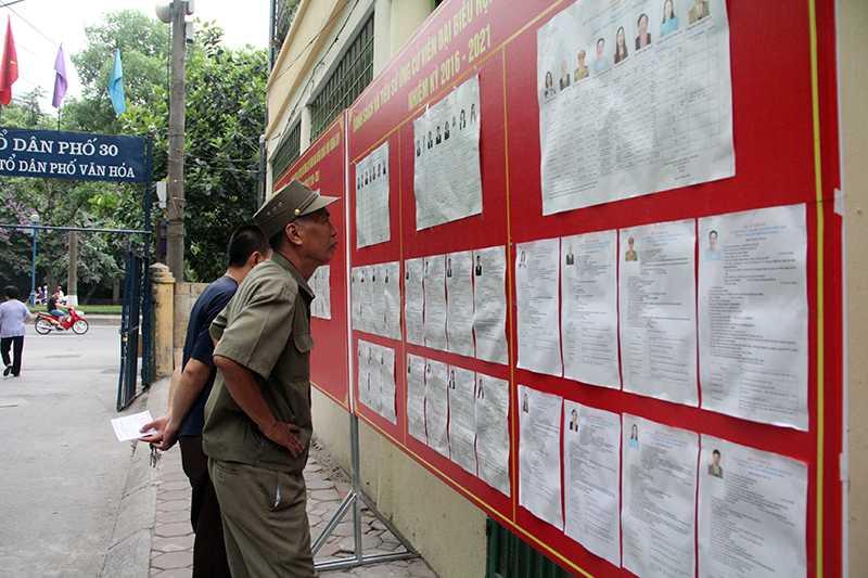 Các cử tri ở phường Nghĩa Đô xem lại tiểu sử các ứng viên trước khi bỏ phiếu