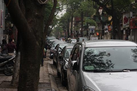 Hàng dài xe ôtô đỗ nối đuôi nhau dưới lòng đường.