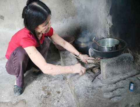 Chị Hà đang nấu bữa cơm trong căn bếp tồi tàn. Ảnh Báo Nghệ An