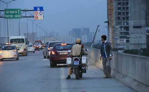 CSGT tuần tra thường xuyên phải nhắc nhở, yêu cầu những người đi bộ di chuyển khỏi mặt đường trên cao.