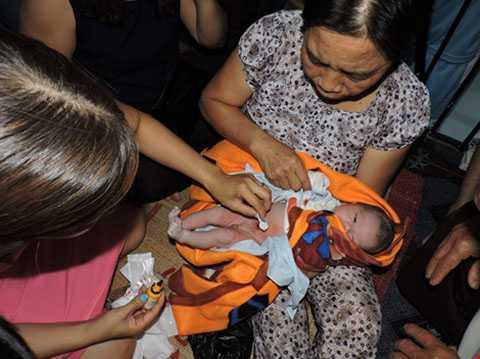 Người dân chăm sóc đứa bé - ảnh VIỆT CƯỜNG
